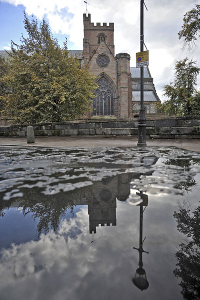 Carlisle Cathedral reflected in puddle.
