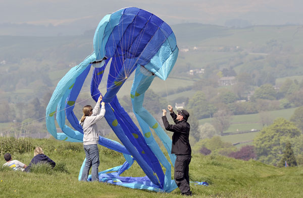 Two people trying to launch a blue Octopus kite.